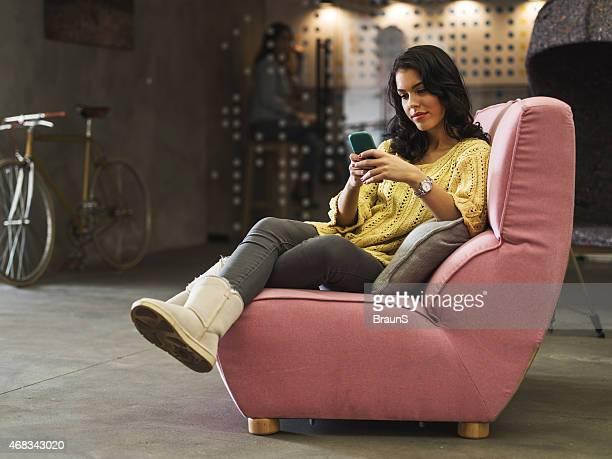 Jeune femme assise dans un fauteuil et de SMS.