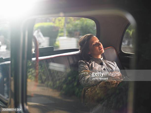 Young woman sitting in back of taxi, looking out window