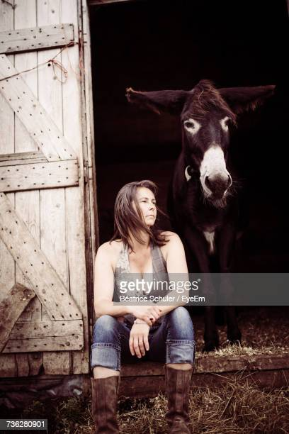Young Woman Sitting In Barn Doorway With Donkey