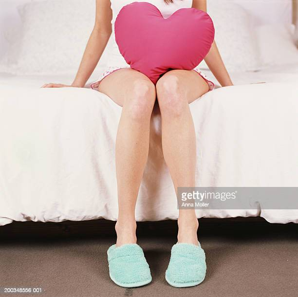 Young woman sitting in bed with heart shaped cushion, low section