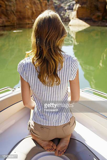 Young woman sitting in boat (rear view)