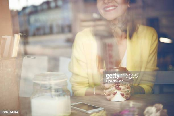 Young woman sitting in cafe, holding coffee cup, tattoos on hand, view through cafe window, mid section