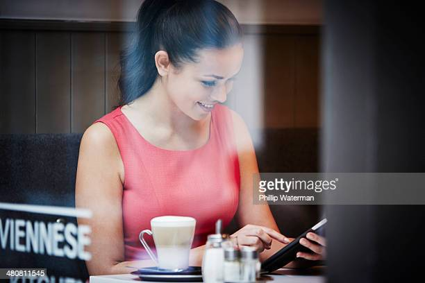 Young woman sitting in cafe with digital tablet and hot drink