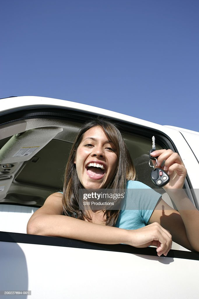 Young woman sitting in car, holding car keys, smiling, portrait : Stock Photo