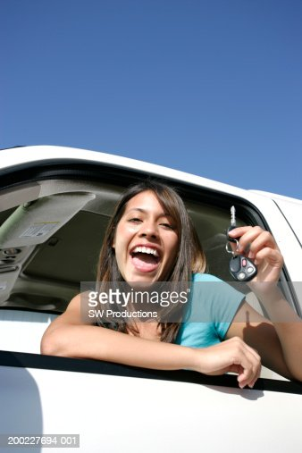 Young woman sitting in car, holding car keys, smiling, portrait : Photo