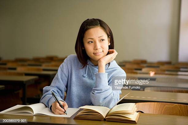 Young woman sitting in classroom, writing, resting head on hand