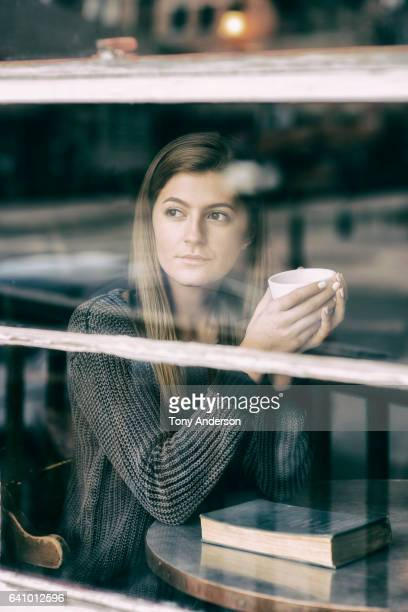 Young woman sitting in coffee shop with book and beverage