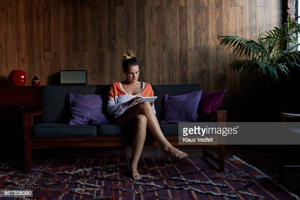 Young woman sitting in couch and using digital tablet