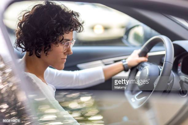 Young woman sitting in drivers seat of a black car. Using navigation device.