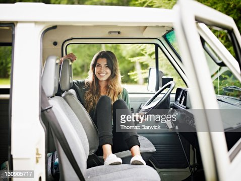 Young woman sitting in drivers seat of van smiling : Stock Photo