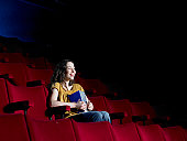 Young woman sitting in empty cinema, laughing