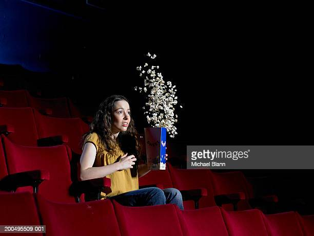 Young woman sitting in empty cinema, popcorn jumping out of box