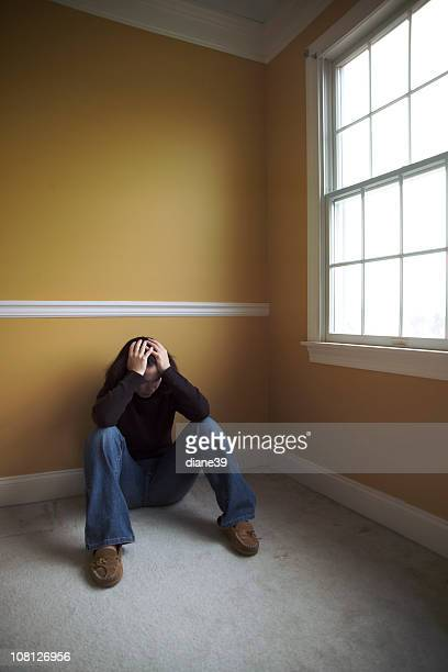 Young Woman Sitting in Empty Room Against Wall