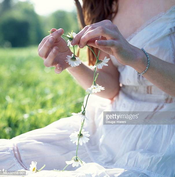 Young woman sitting in field making daisy chain, mid section
