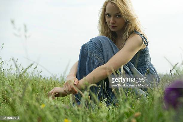 Young woman sitting in field of grass, portrait
