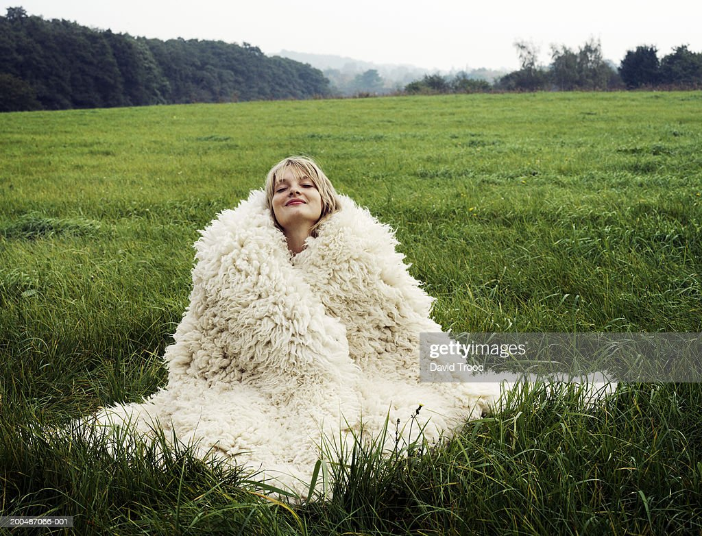 Young woman sitting in field wrapped in wool blanket, eyes closed