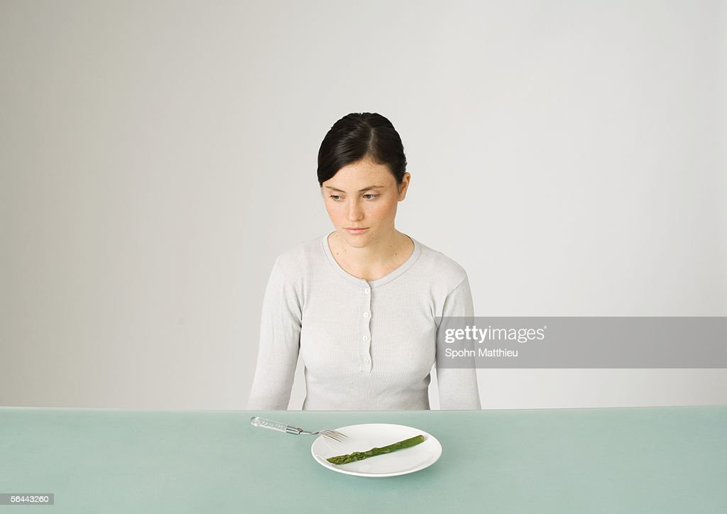 Young woman sitting in front of plate with single asparagus, looking away
