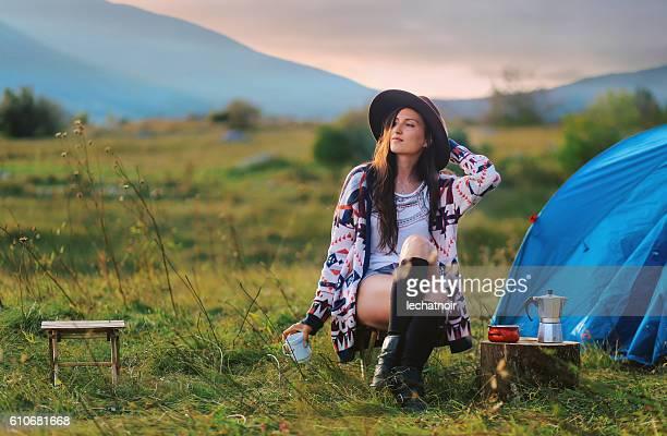 Junge Frau sitzt auf der Vorderseite von Zelt