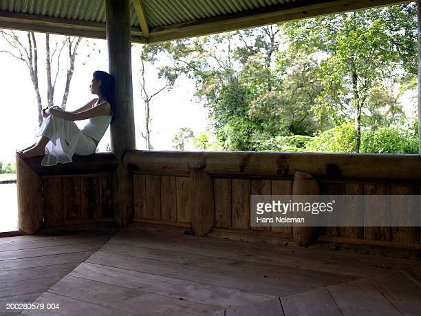 Young woman sitting in gazebo, side view