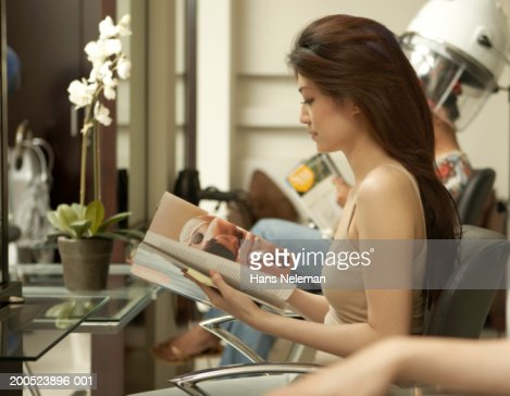 Young woman sitting in hair salon reading magazine side for Reading beauty salon