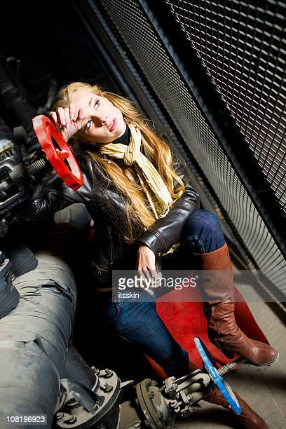 Young Woman Sitting in Industrial Pipes
