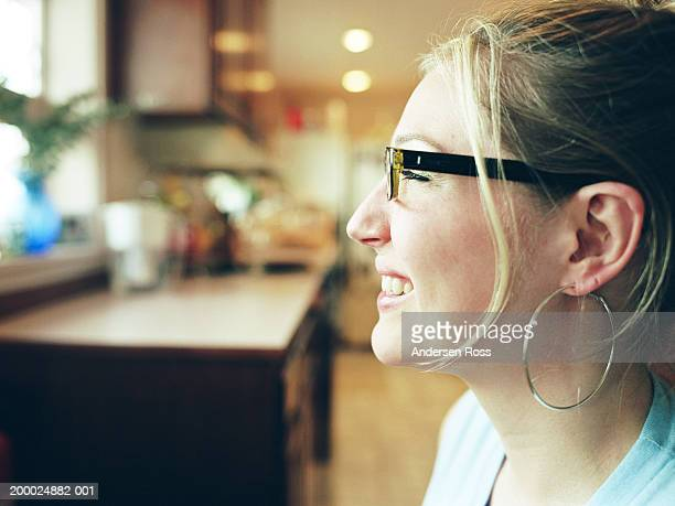 Young woman sitting in kitchen, profile, close-up