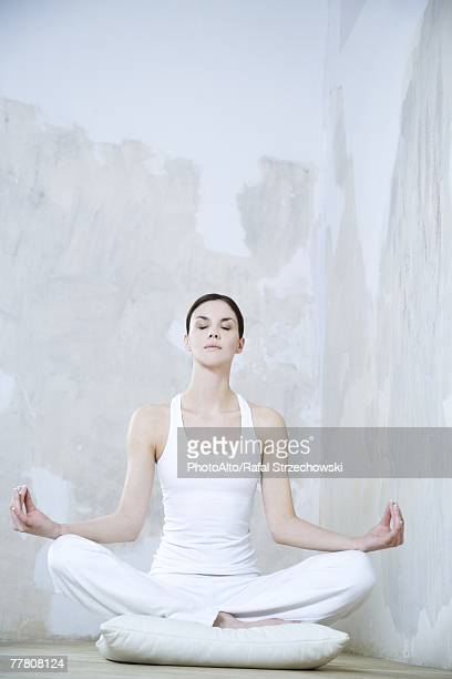 Young woman sitting in lotus position, eyes closed, full length