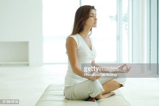 Stock Photography of Young woman sitting in lotus position