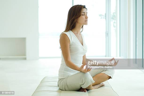 Young woman sitting in lotus position, eyes closed, side view