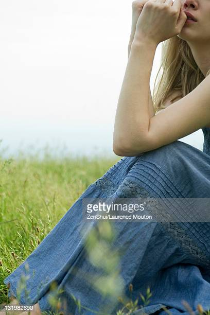 Young woman sitting in meadow, hands under chin, cropped