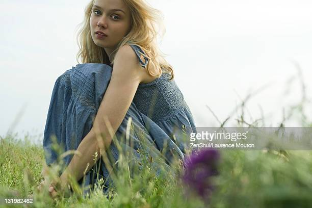 Young woman sitting in meadow, portrait