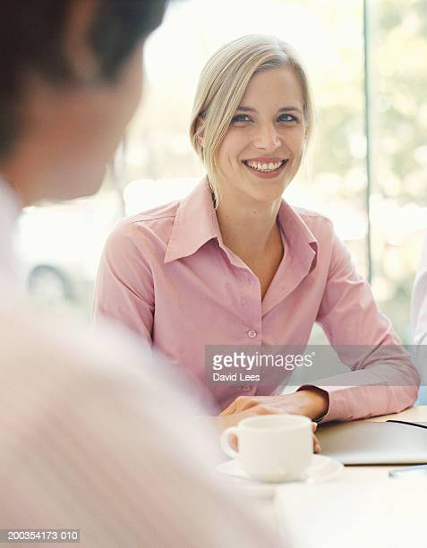 Young woman sitting in meeting, smiling (focus on woman)