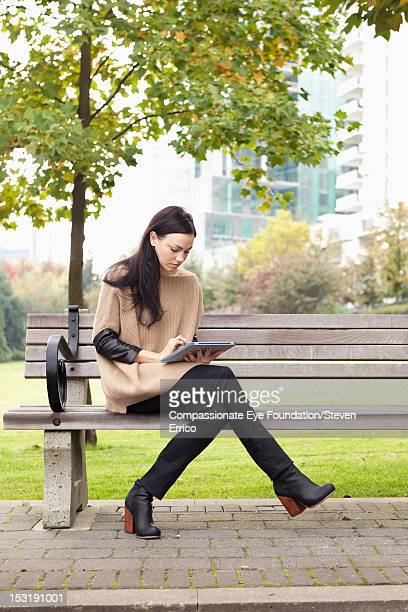 Young woman sitting in park using digital tablet