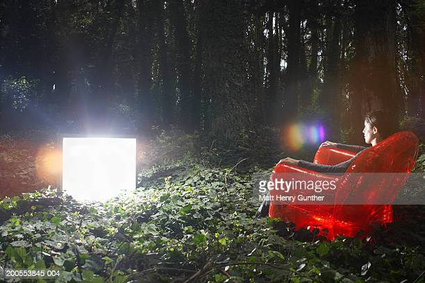 Young woman sitting in red chair in forest, watching television screen