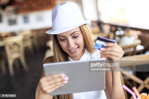 Young woman sitting in restaurant and using credit card