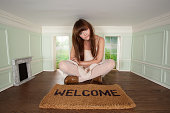 Young woman sitting in small room with welcome mat