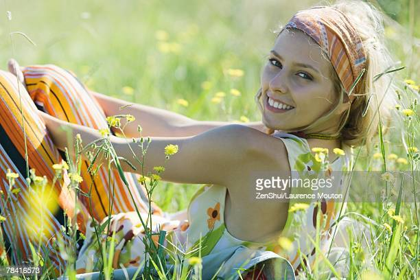 Young woman sitting in tall grass with knees up, smiling over shoulder at camera