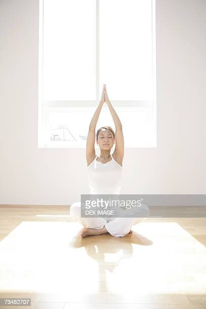Young woman sitting in the lotus position and practicing yoga
