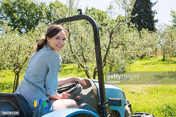 Young woman sitting in tractor looking over shoulder at camera smiling