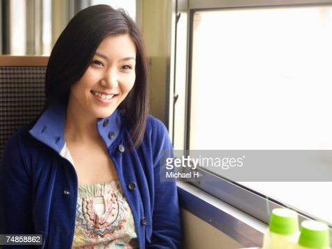 Young woman sitting in train compartment, smiling : Stock Photo