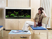 Young woman sitting in waiting room, side view
