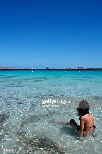 Young woman sitting in water in Costa Smeralda