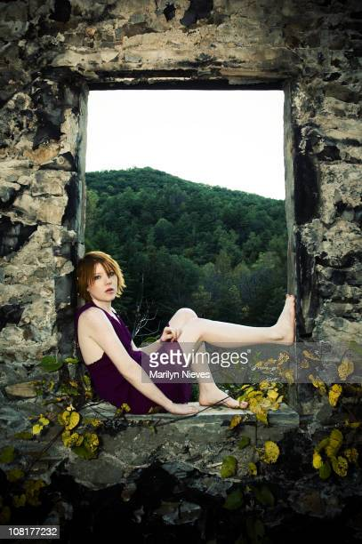 Young Woman Sitting in Window Frame