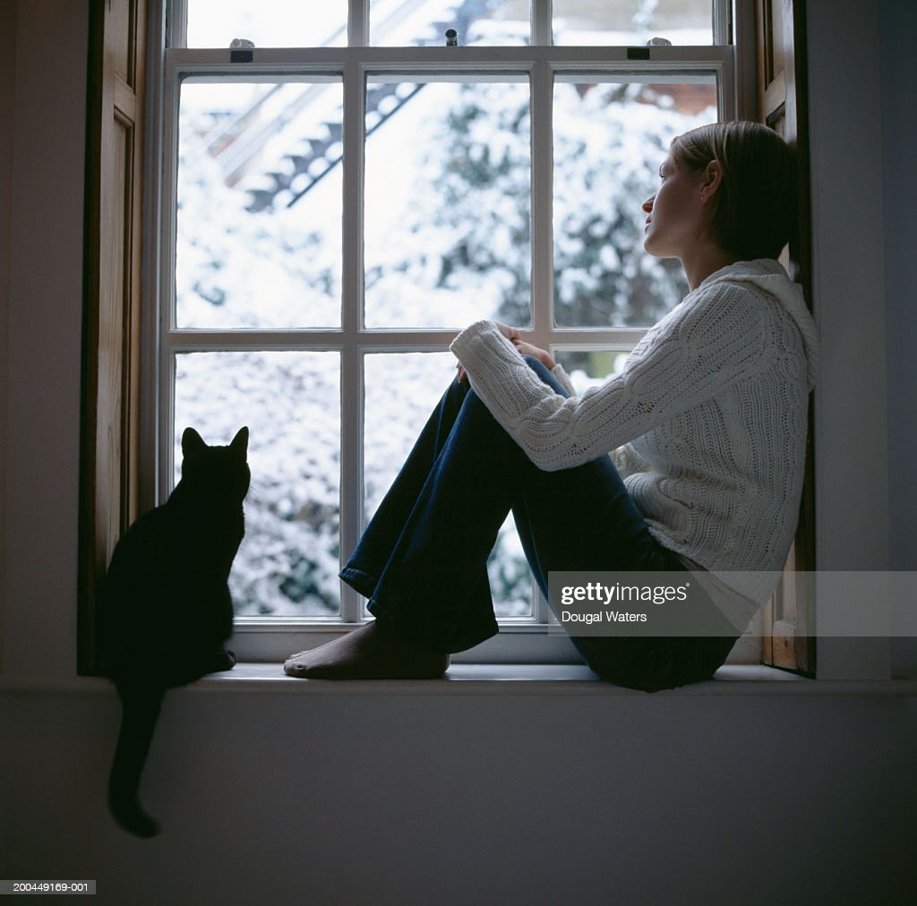 Young Woman Sitting In Window With Cat Looking Outside