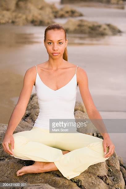 Young woman sitting in yoga position on rock at beach, portrait