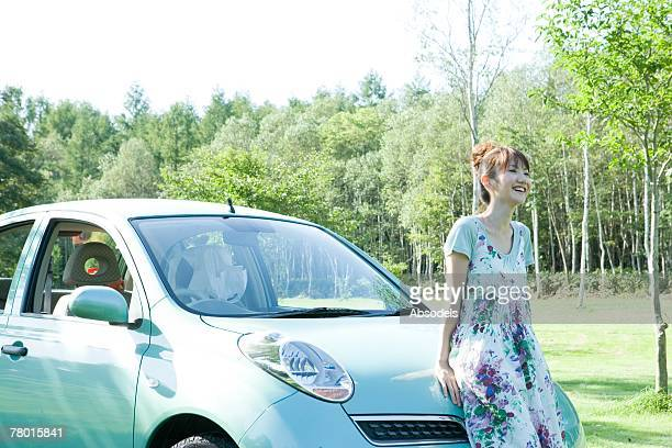 Young Woman sitting leaning against car in forest