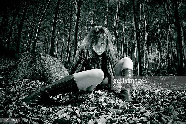 Young Woman Sitting Leaves on Forest Floor, Toned