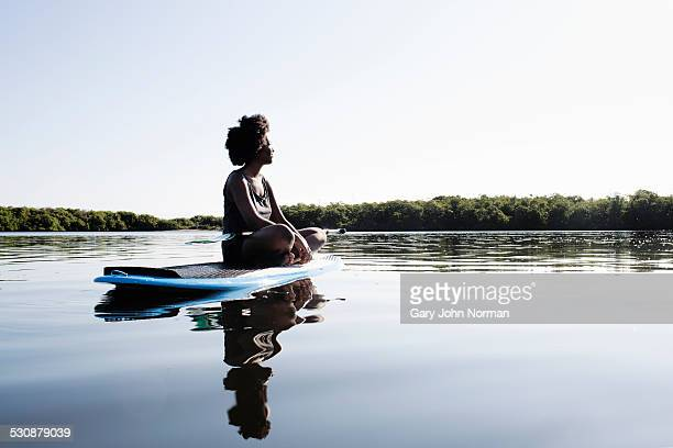 Young woman sitting legs crossed on paddle board.