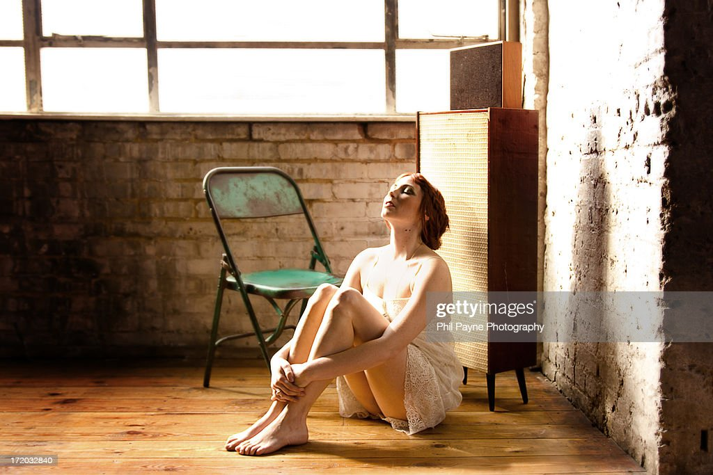 Young woman sitting listening to music : Stock Photo