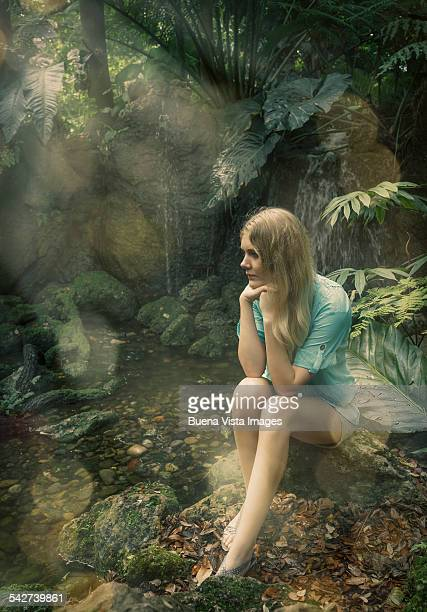 Young woman  sitting near a creek in a forest
